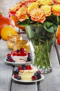 Layer cakes decorated with fresh fruits on rustic wooden table.
