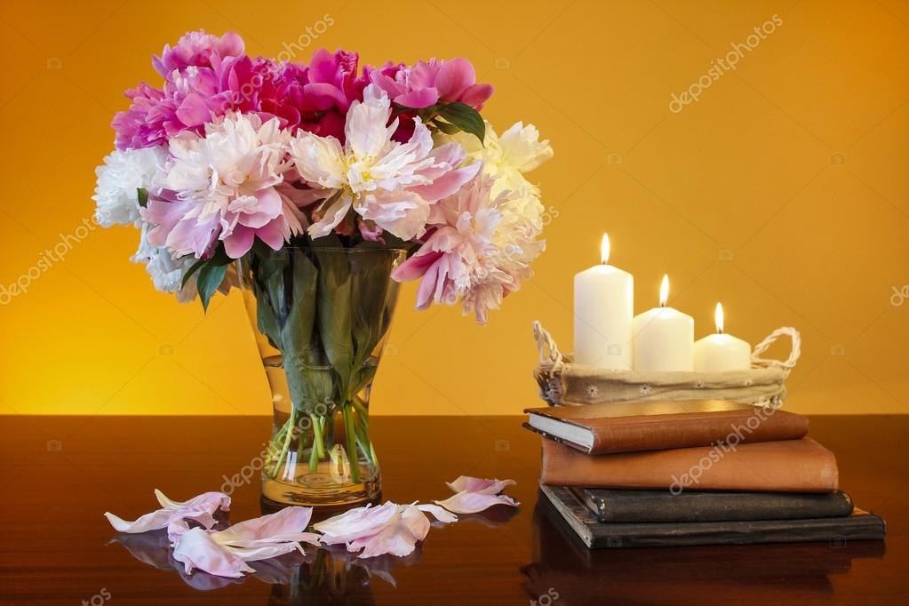 Bouquet of peonies in glass vase and basket of candles on wooden