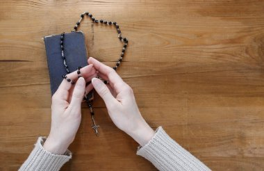 Hands with rosary over old Holy Bible. Wooden background.