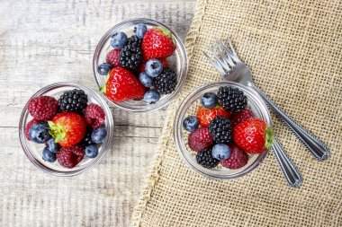 Top view of fruit salad in small transparent bowls on wood