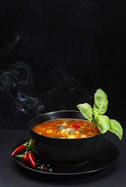 Tomato soup decorated with basil leaf on black background