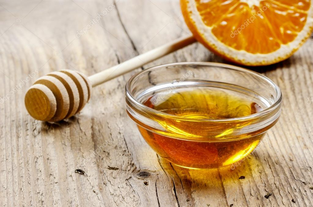 Bowl of honey on wooden table. Symbol of healthy living
