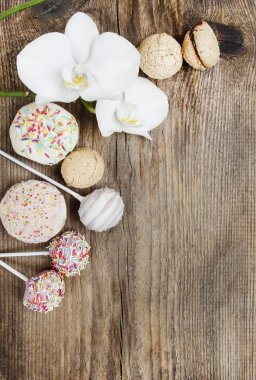 Top view of cake pops, muffins, cupcakes and macarons