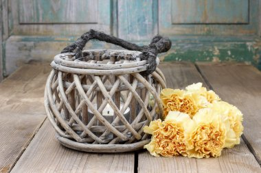 Vintage lantern and bouquet of yellow carnations on rustic woode