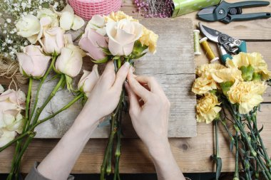 Florist at work. Woman making wedding bouquet of pink roses and