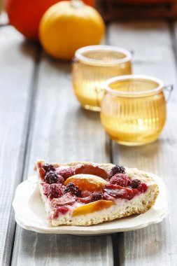 Piece of blueberry, peach and plum cake on rustic wooden table