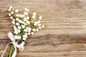 Fotografie Lily of the valley flowers on wooden background.