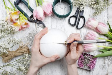 Florist workplace: woman making floral arrangements with polystyrene florist ball stock vector