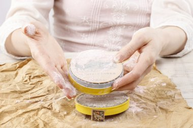 Woman holding vintage compact powder in beautiful hands