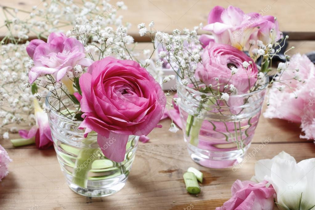 Florist workplace: incomplete tiny bouquets in glass vases. Step ...