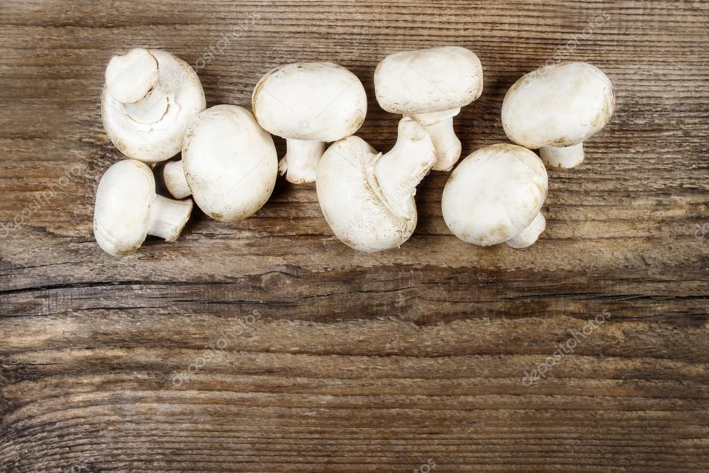 Top view of agaricus mushroom on wooden table. Copy space, blank