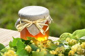 Fotografie Jar of fresh and delicious honey with linden flowers