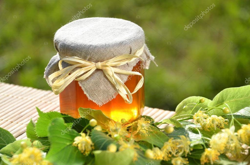 Jar of fresh and delicious honey with linden flowers