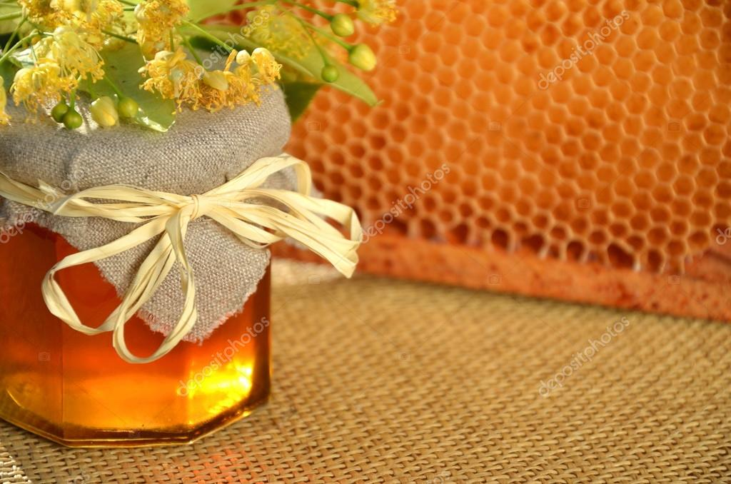 Jar of fresh and delicious honey with linden flowers and honeycomb