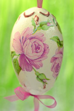 Easter egg decorated with flowers made by decoupage technique on green background