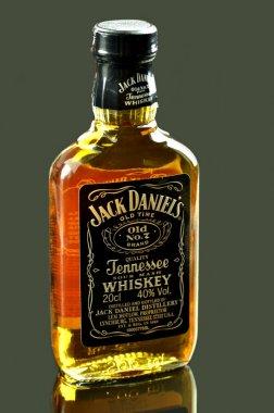 Small bottle of Jack Daniels whiskey isolated on dark background