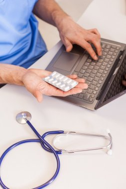 Doctor using laptop and holding pills