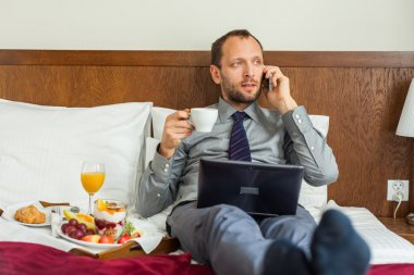 Businessman using phone and laptop during breakfast