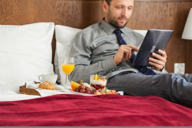 Businessman using tablet during breakfast