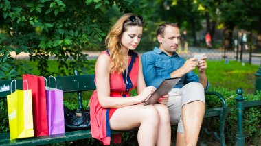 Couple sitting on bench and using digital gadgets