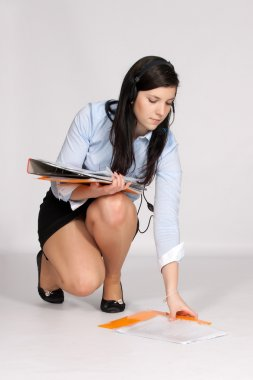 Young woman in mini skirt and blouse, squatting rises from the g