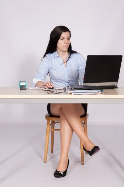 Female poses behind a desk in the office