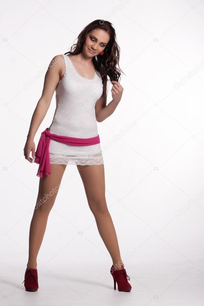 142f77328 Mujer joven en un mini vestido blanco, tacones rojos con bufanda ...