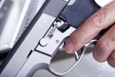VExtreme close up of a left hand of a mature adult man holding a 9mm handgun with his finger on the trigger, and a defocused laptop computer in the background. Backlit. Shallow depth of field. stock vector