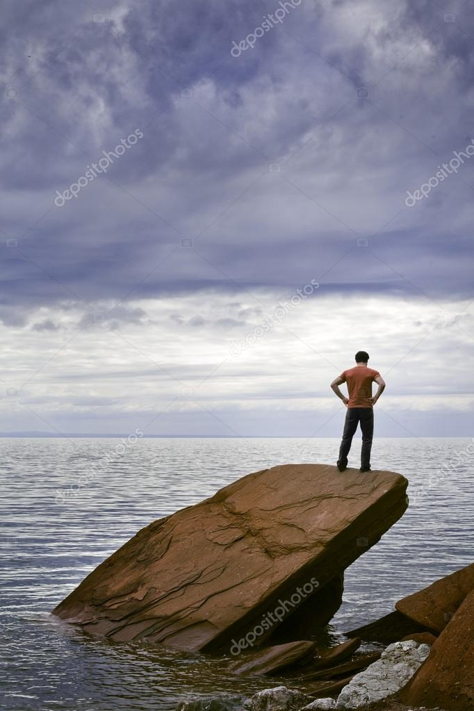 A young man stands on a rock by the sea