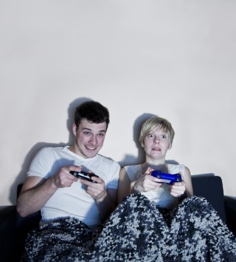 Young couple playing video games comfortably wrapped in a blanket.