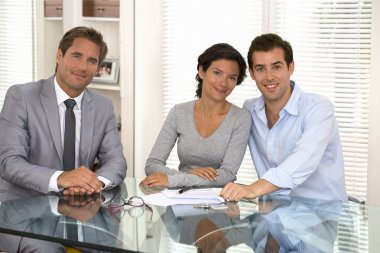 Happy young couple signing financial contract, looking camera