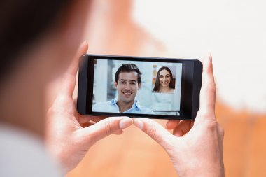 Closeup of a female hand holding a smartphone during a skype vid