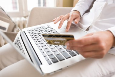Close-up woman's hands holding a credit card and using computer