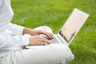 Woman hands typing on a laptop keyboard, in garden