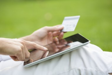 Close-up woman's hands holding a credit card and using tablet pc