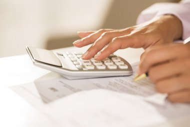Woman's hands with a calculator and pen, Accounting.