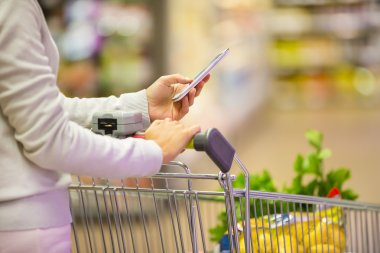 Woman using mobile phone while shopping in supermarket