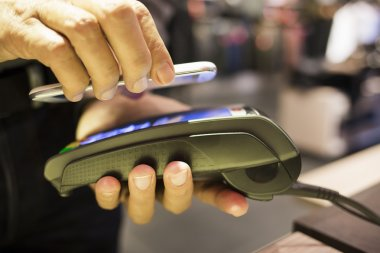 Man paying with NFC technology on mobile phone, in clothing stor