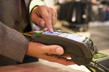 Man pay by credit card in clothing store