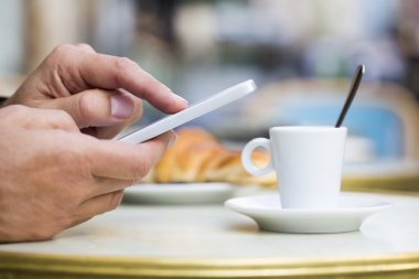 Man using a cell phone on cafe terrace, croissant and coffee