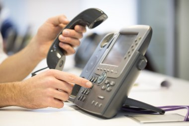 Man hand dialing phone number