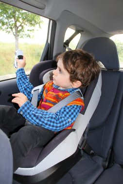 Baby in car seat for safety, playing with toy car