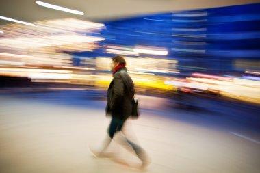 A shopper walking against shop window