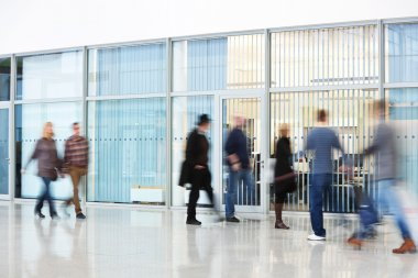 Unrecognizable People Walking in Modern Corridor