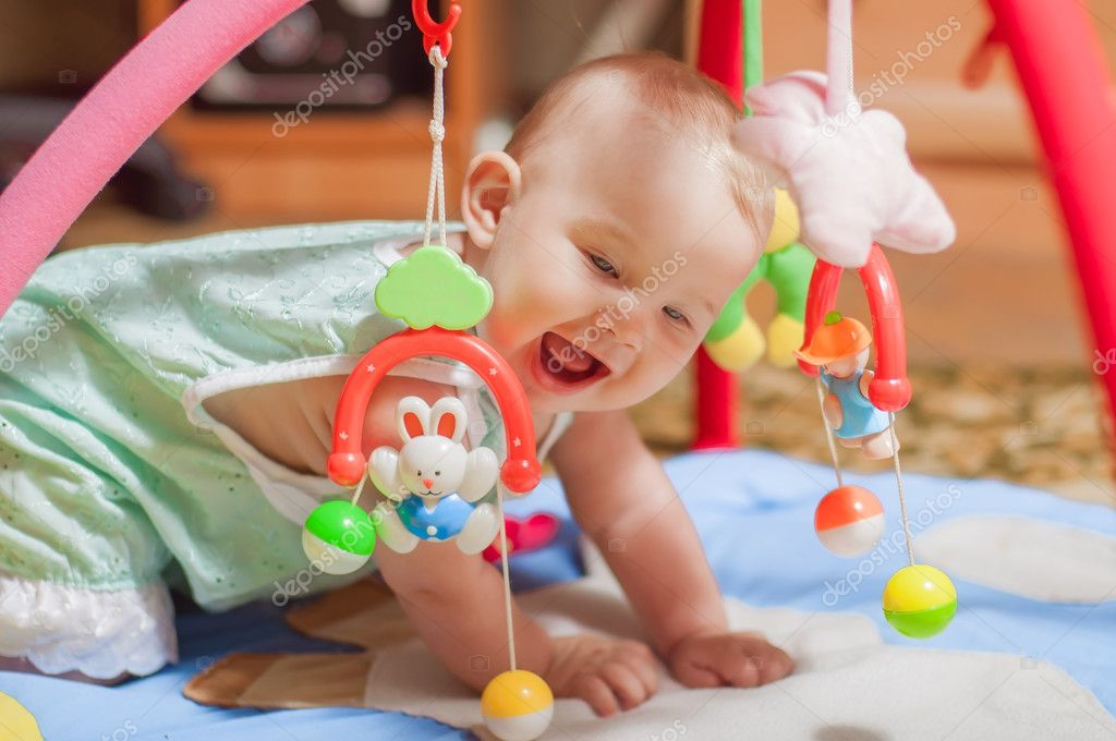 Little baby playing with toys at home