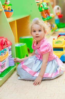 Little girl with toys in the playroom