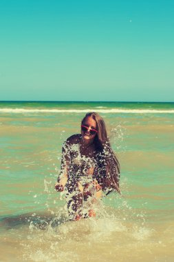 Young girl in the sea water splashes and smiling