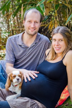 Happy family with their dog and pregnant motherin park