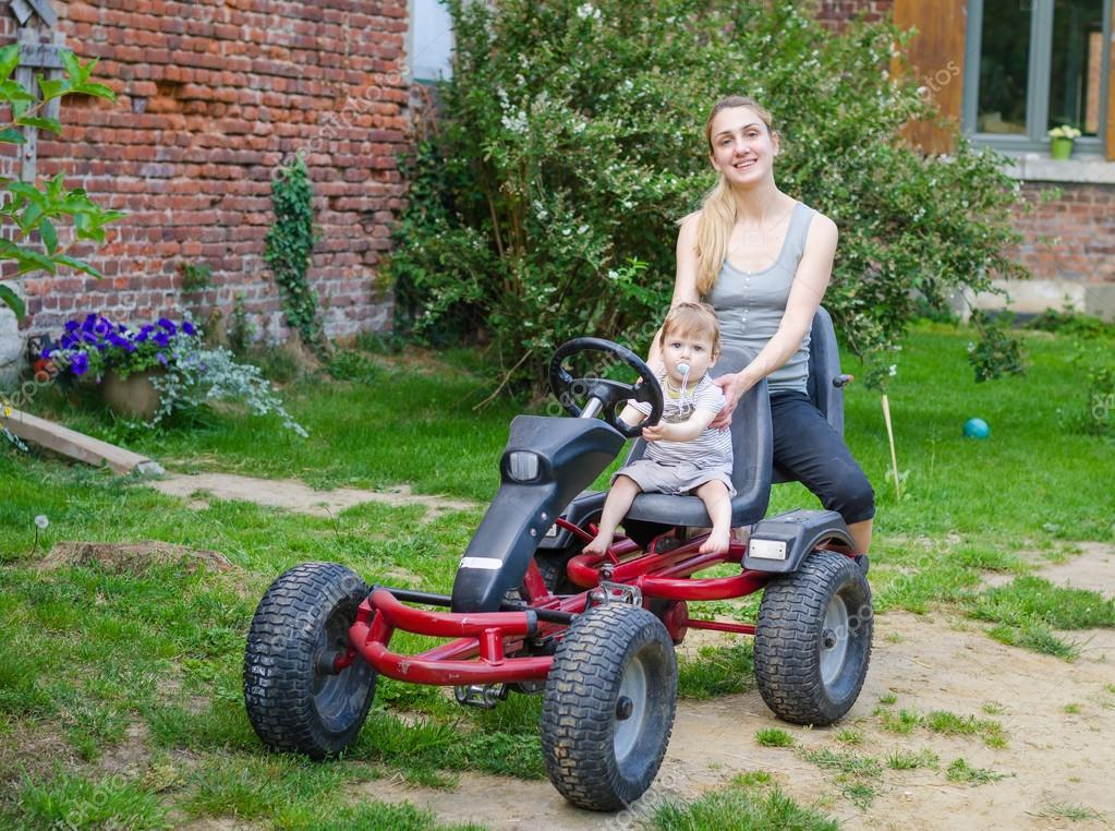 Little cute boy driving pedal car with young mother