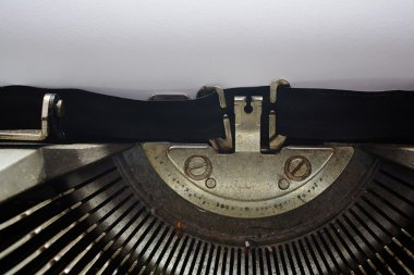 A Closeup image of the typebars and ribbon of an old style typewriter and paper